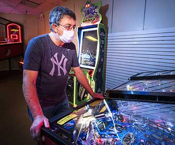 Stroke survivor wearing a mask plays pinball in an arcade.