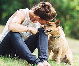 Woman plays with dog outside.
