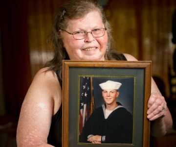 Woman holding picture frame of her son in military uniform