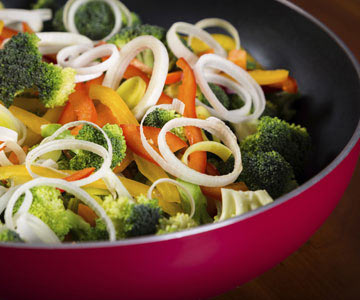 A pan full of stir-fried onions, broccoli and bell pepper.