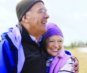 Smiling couple outdoors, dressed in stocking caps.