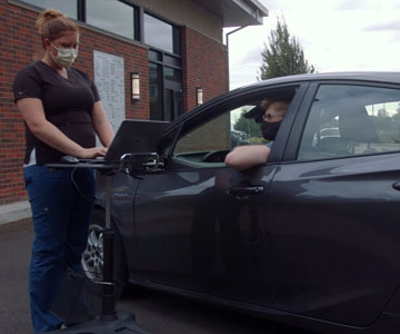 A nurse wearing a face mask speaks to a person wearing a face mask while they sit in their vehicle.