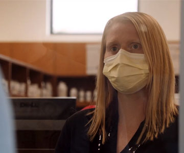 A woman with her hair down wearing a face mask.