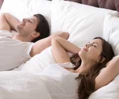 Couple laying in bed focusing on breathing
