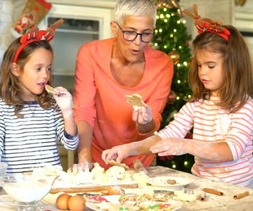 Mature woman making cookies with grandchildren.