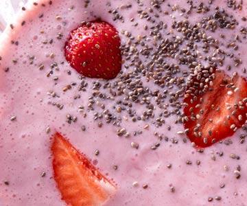 A close-up of a strawberry smoothie with chia seeds.