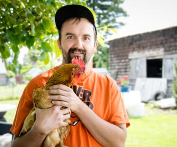 Anthony holding one of his chickens.