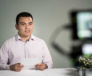 Hispanic male wearing long-sleeved light pink button down shirt reads script to a video camera