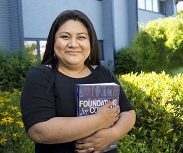 Hispanic female health care worker wearing black top and holding a book titled Foundation for Community Health Workers stands in front of a blue painted building