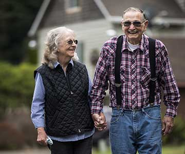 Senior grey haired woman walks holding hands with senior grey-haired smiling man.