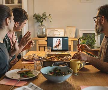 A family sits around a set table with a tablet showing someone having dinner with them virtually