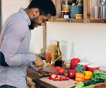 Smiling Black male with beard wearing cross-hatched patterned shirt cuts red bell peppers on a cutting board with a variety of vegetables