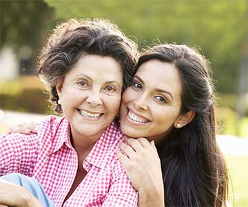 Older dark and grey haired woman is hugged from behind by her long dark-haired daught.