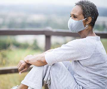 An older person of color wears a mask while sitting outside