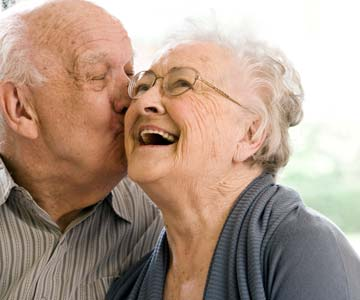 Senior man kissing happy woman