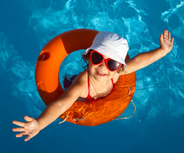 Little girl in swimming pool using life preserver.