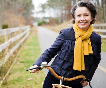 smiling woman on bike wearing a scarf