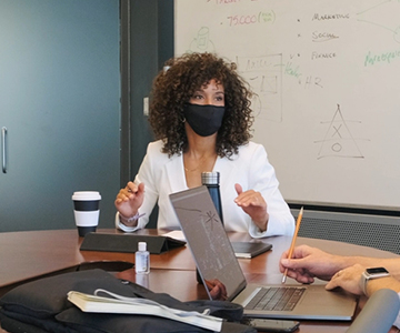 Woman at a work meeting wearing a mask.