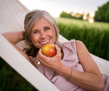 A smiling silver haired woman lays in a hammock while eating a red apple