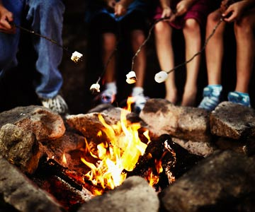 Campers roasting marshmallows around a campfire.
