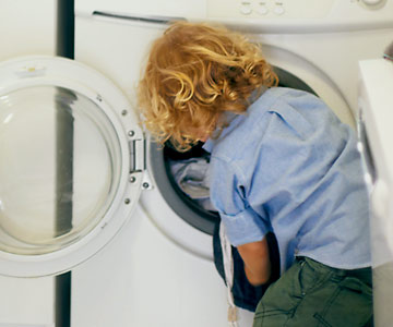 Young child helping with laundry.