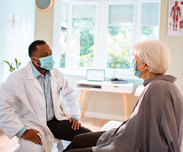 Doctor and patient talking. Each is wearing a mask.