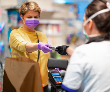 Woman paying for groceries while wearing mask.