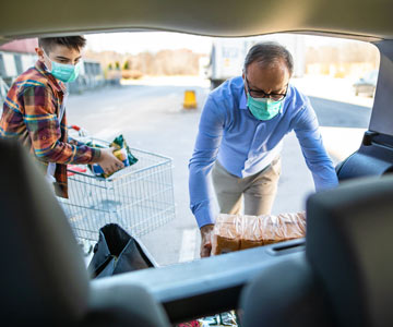 Father and son loading groceries into car while wearing masks.