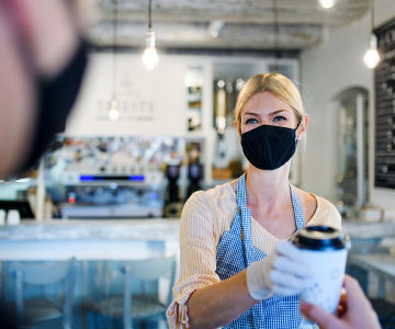 Barista handing coffee to customer while wearing a mask.