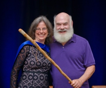 Dr. Eckroth receiving a ceremonial walking stick from Dr. Weil.