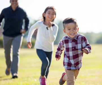 Young boy laughing while being chased in a park by his older sister and dad