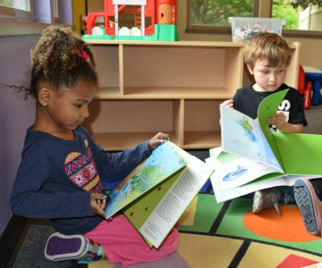 Black girl and white boy preschoolers reading new colorful books