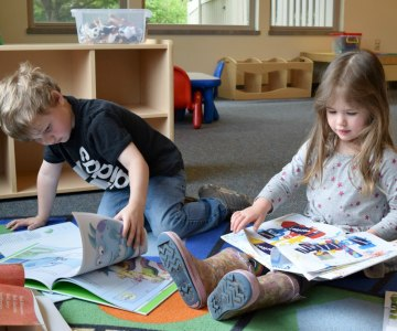 Preschool boy and girl on the flooring absorbed in looking at new picture books