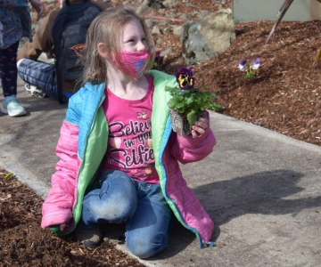Elementary age girl wearing a pink T-shirt that says Believe in Your Selfie and holding a pretty potted flowering plant while kneeling down to plant it.