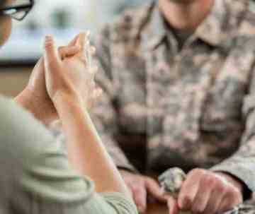 Image of female consulting with a man in military fatigues