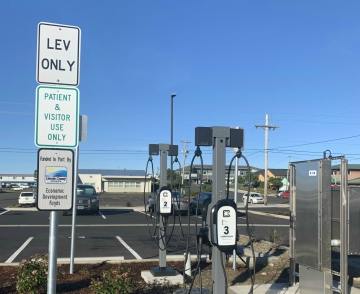 View of grant funding sign by electric vehicle charging station at SPCH