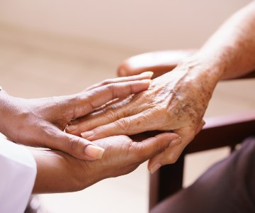 A pair of younger looking hands hold a part of older hands to illustrate a sense of caring