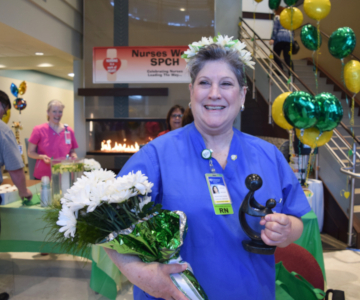 Smiling nurse Cecilia Caryl, wearing blue scrubs holds a bouquet of white daisies, and wears a headband decorated in daisies