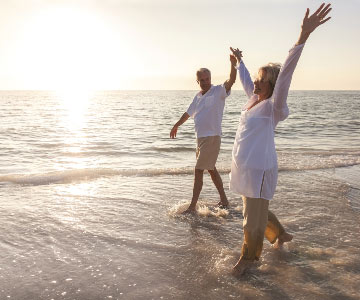 An older Caucasian couple wading in the ocean at sunset, their arms upraised in victory