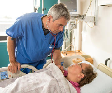 A man in blue scrubs attends to a woman patient lying in a hospital bed