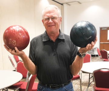 Class participant holds a bowling ball in each representing his total weight loss