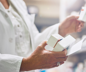 Close up of woman in white lab coat holding boxes of medication