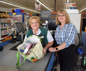 JC Market employees Linda Plaster and Diane Mattson show an open grocery tote filled with protein items