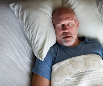 Man with grey beard and wearing blue t-shirt asleep on white pillow