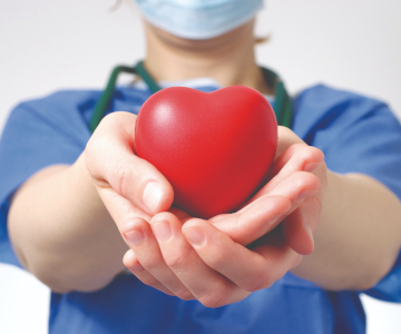 surgeon in blue scrubs with mask holds a small red heart icon in outstretched hands