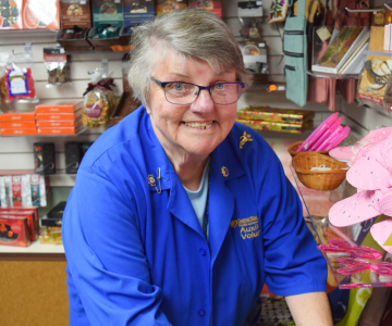 Gloria Mazzeo, wearing her blue volunteer jacket, straightens up items on the Gift Shop shelf