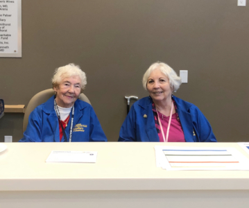 two older women wearing blue volunteer jackets sit at the hospital guest services desk ready to help