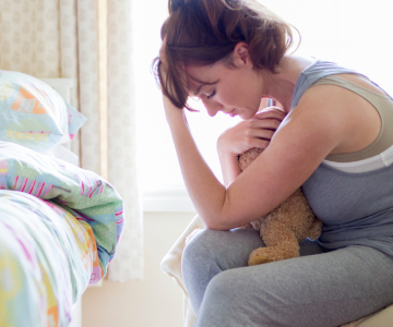 Woman gripping a teddy bear to her chest bends in grief beside a bed