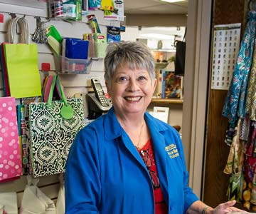 Volunteer Becky Lockett stands at gift shop cash register