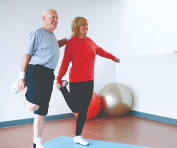 older couple each wearing exercise clothes, stand on one foot